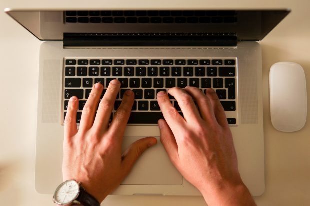 Hands typing at a laptop keyboard