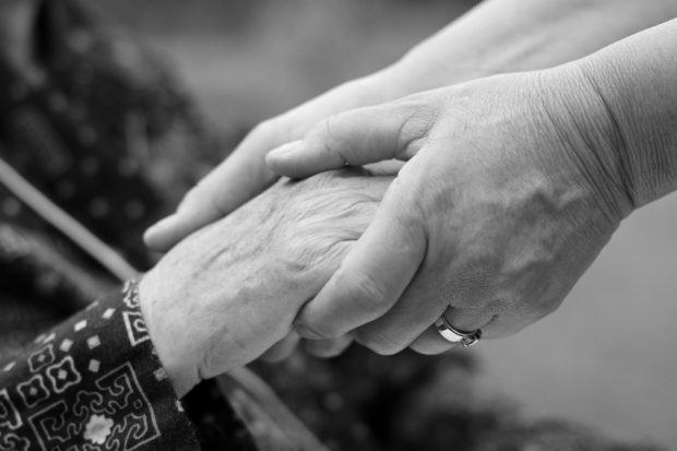 Doctor's hand holding an elderly hand