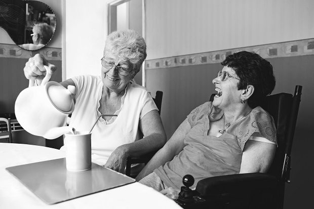 Two women laughing while having a cup of tea