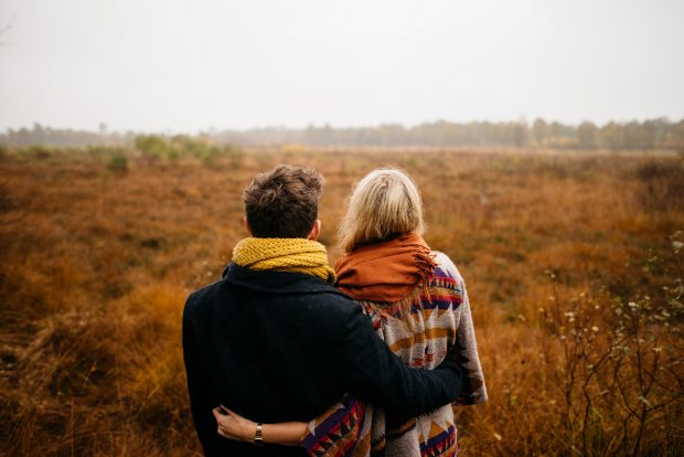 A man and a woman standing in a field