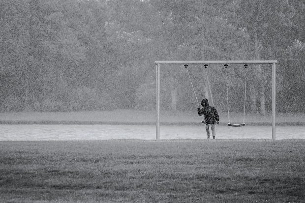 Boy in a park sitting on a swingset in the rain
