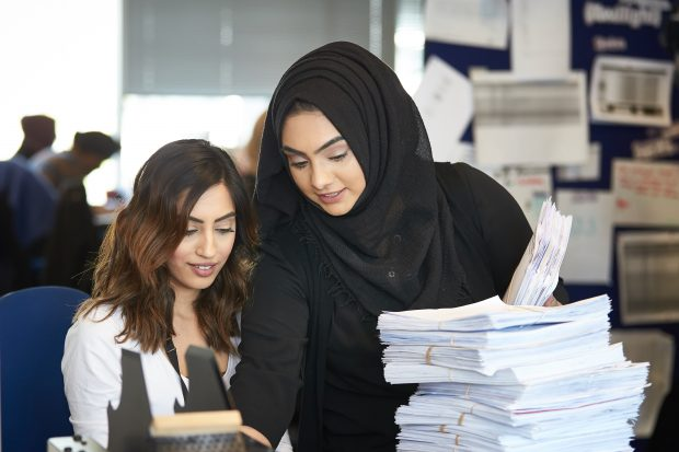 Two young women looking over a document next to a stack of completed documents.