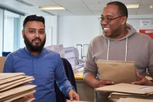 Two men with piles of brown envelopes